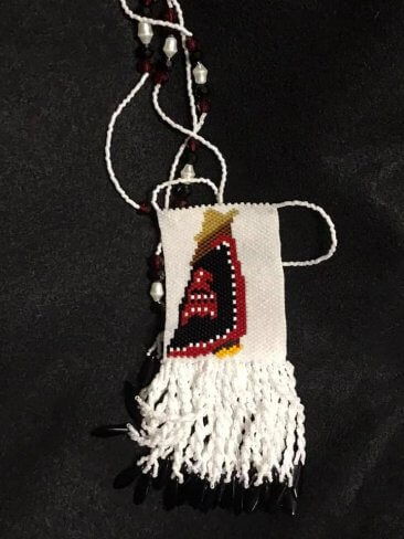 beaded Haida necklace featuring woman wearing yellow cedar hat and button blanket